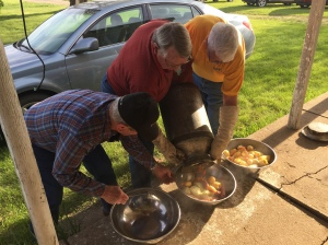 The men pouring out the food prepared in a milk can. Delicious!