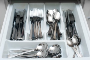 a kitchen cutlery drawer full of knives, forks and spoons